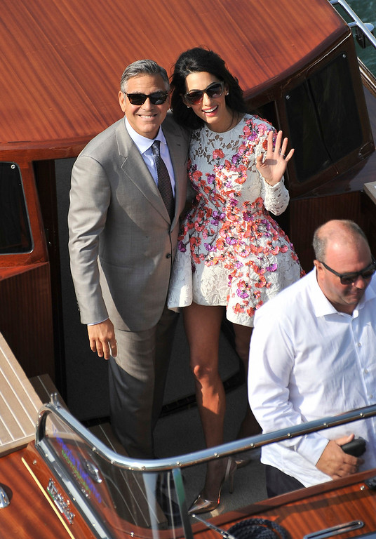 . George Clooney and his wife Amal Alamuddin, cruise the Grand Canal after leaving the Aman luxury Hotel in Venice, Italy, Sunday, Sept. 28, 2014. George Clooney married human rights lawyer Amal Alamuddin Saturday, the actor\'s representative said, out of sight of pursuing paparazzi and adoring crowds. (AP Photo/Luigi Costantini)