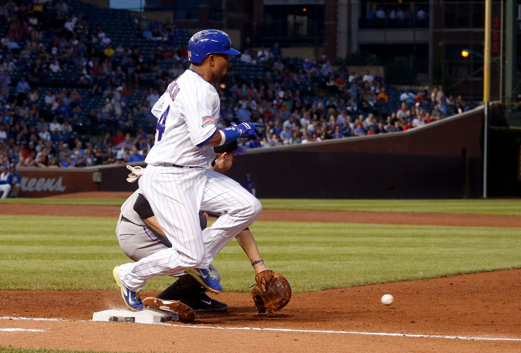 . Chicago Cubs\' Emilio Bonifacio beats the throw from Colorado Rockies second baseman DJ LeMahieu to first baseman Justin Morneau, during the second inning of a baseball game Tuesday, July 29, 2014, in Chicago. (AP Photo/Charles Rex Arbogast)