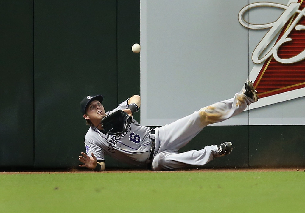 . PHOENIX, AZ - JULY 05:  Outfielder Corey Dickerson #6 of the Colorado Rockies makes a catch as he falls against the wall during the sixth inning of the MLB game against the Arizona Diamondbacks at Chase Field on July 5, 2013 in Phoenix, Arizona.  (Photo by Christian Petersen/Getty Images)