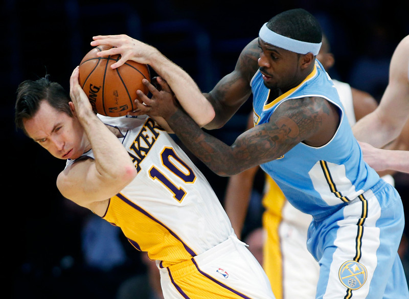 . Los Angeles Lakers\' Steve Nash (L) and Denver Nuggets\' Ty Lawson fight for the ball which resulted in a jump ball called during the first half of their NBA basketball game in Los Angeles January 6, 2013. REUTERS/Danny Moloshok