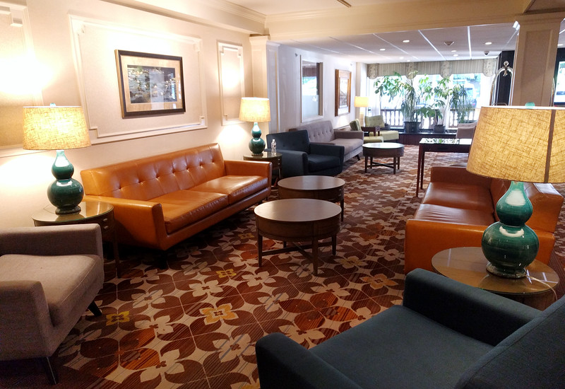 Lobby of the Radnor Hotel has brown printed carpet, comfy leather sofas in several seating arrangements.