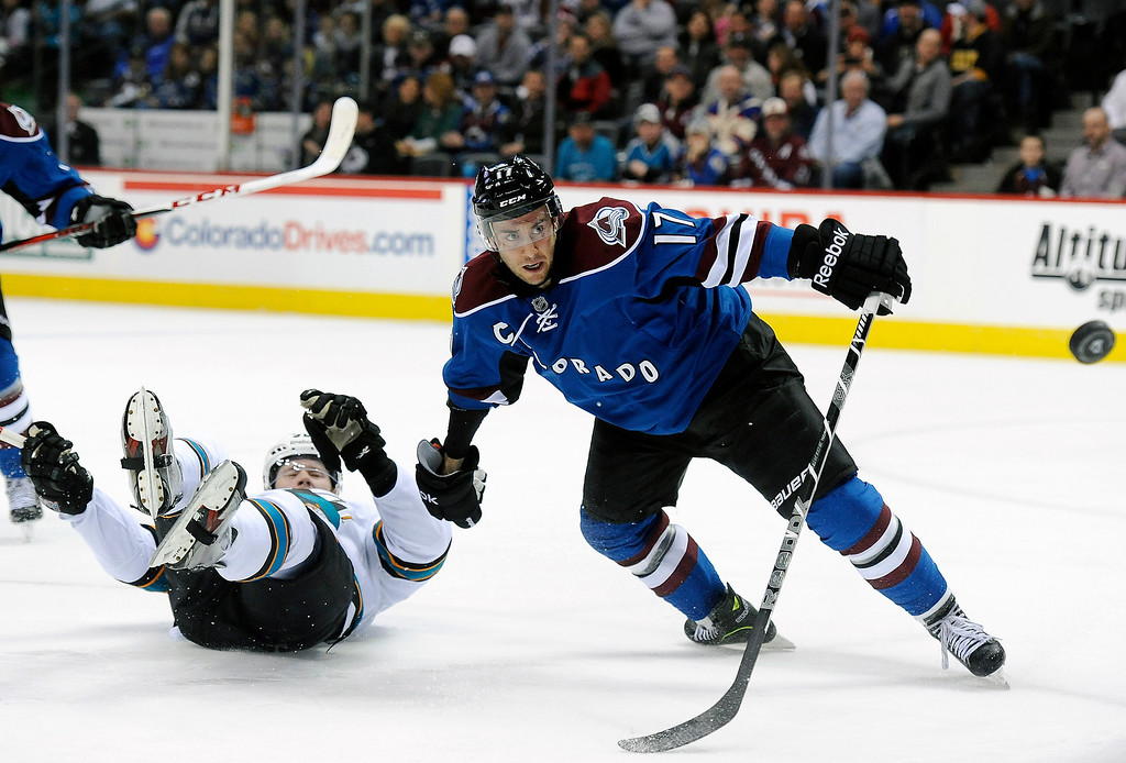 . San Jose Sharks defenseman Matt Irwin, left, falls to ice fighting for the puck with Colorado Avalanche right wing Aaron Palushaj, right, in the third period of an NHL hockey game on Sunday, March 10, 2013, in Denver. The Avalanche won 3-2 in overtime. (AP Photo/Chris Schneider)