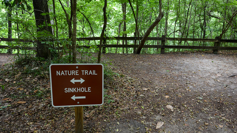 Nature Trail sign with fence behind it