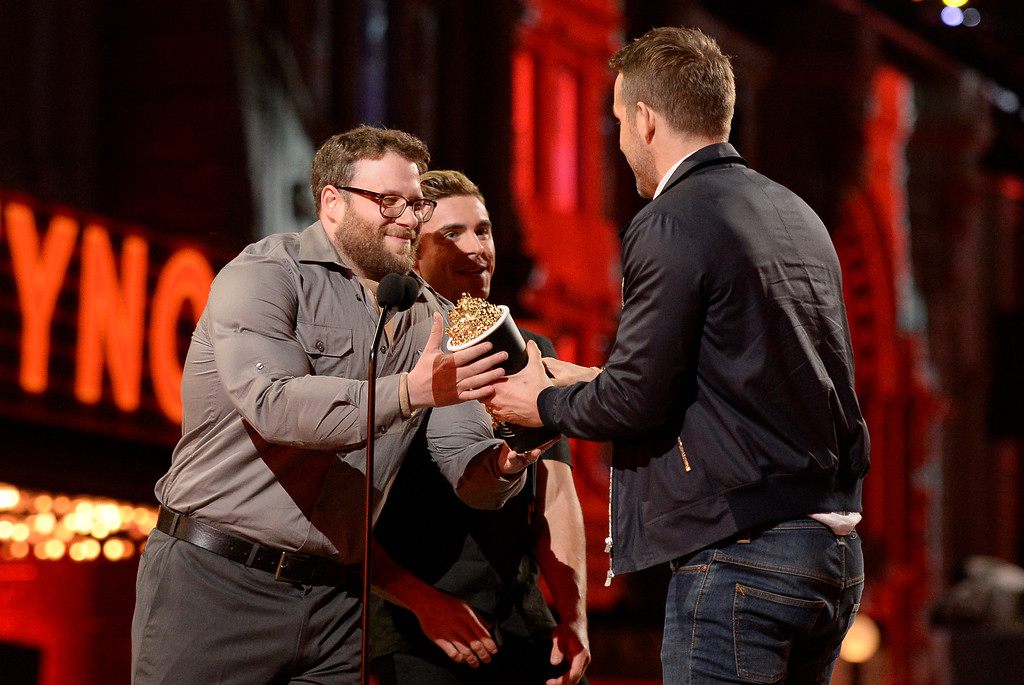 . Seth Rogen, left, and Zac Efron present the award for best comedic performance to Ryan Reynolds, right, at the MTV Movie Awards at Warner Bros. Studio on Saturday, April 9, 2016, in Burbank, Calif. (Kevork Djansezian/Pool Photo via AP)