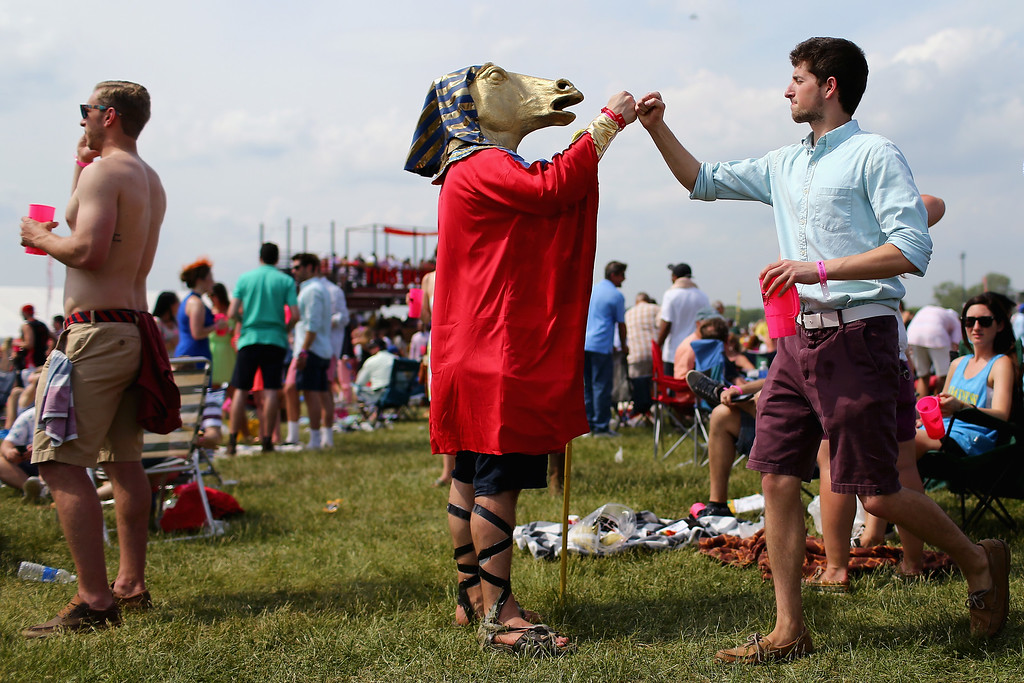 . Mike Calimano of Valley Stream, NY, fist bumps a race fan in his American Pharoah costume in the infield prior to the 140th running of the Preakness Stakes at Pimlico Race Course on May 16, 2015 in Baltimore, Maryland.  (Photo by Maddie Meyer/Getty Images)