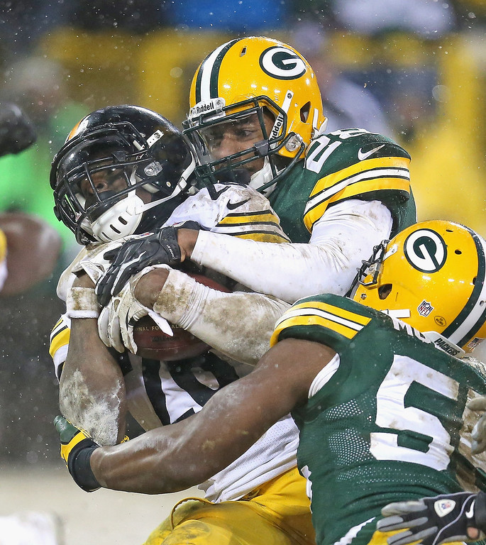 . Le\'Veon Bell #26 of the Pittsburgh Steelers is stopped just short of the goalline by Sean Richardson #28 and Andy Mulumba #55 of the Green Bay Packers at Lambeau Field on December 22, 2013 in Green Bay, Wisconsin.  The Steelers defeated the Packers 38-31.  (Photo by Jonathan Daniel/Getty Images)