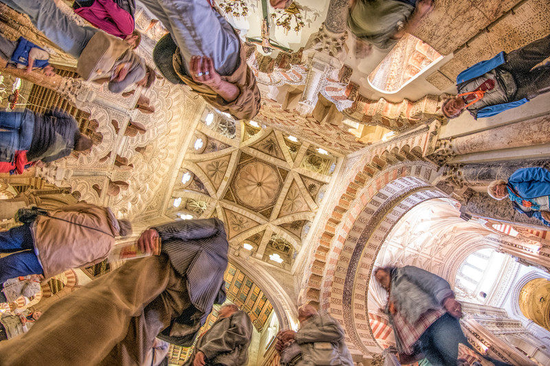Low angle view of visitors below the dome of the Chapel of Villaviciosa, a 15th century Christian work inside the moorish Mosque of Cordoba, Spain.