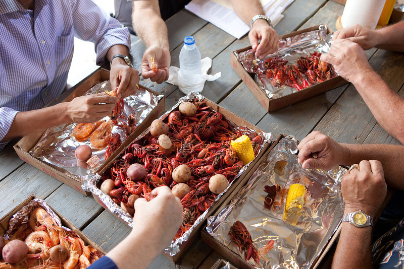 ". June 4, 2010 ""To call attention to the safety of the seafood in the Gulf Coast, the President ate some shrimp and crawfish with locals in Grand Isle, Louisiana. I noticed all the hands digging into the food and thought it made an interesting angle.\"" (Official White House Photo by Pete Souza)"