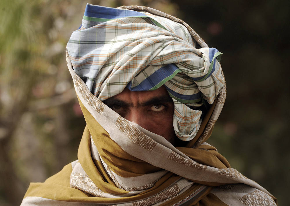 Description of . A former Taliban fighter looks on after joining Afghan government forces during a ceremony in Herat province on March 26, 2012. Twelve fighters left the Taliban to join government forces in western Afghanistan. The Taliban, ousted from power by a US-led invasion in the wake of the 9/11 attacks, announced earlier this month that they planned to set up a political office in Qatar ahead of talks with Washington. AFP PHOTO / Aref Karimi/AFP/Getty Images