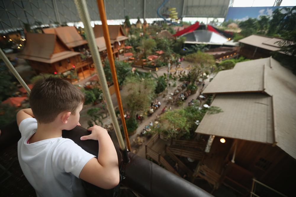 . A young boy rides in the basket of a balloon as he looks down at the Thai House (L) and other restaurants located in the Tropical Islands indoor resort on February 15, 2013 in Krausnick, Germany. Located on the site of a former Soviet military air base, the resort occupies a hangar built originally to house airships designed to haul long-distance cargo. Tropical Islands opened to the public in 2004 and offers visitors a tropical getaway complete with exotic flora and fauna, a beach, lagoon, restaurants, water slide, evening shows, sauna, adventure park and overnights stays ranging from rudimentary to luxury. The hangar, which is 360 metres long, 210 metres wide and 107 metres high, is tall enough to enclose the Statue of Liberty.  (Photo by Sean Gallup/Getty Images)