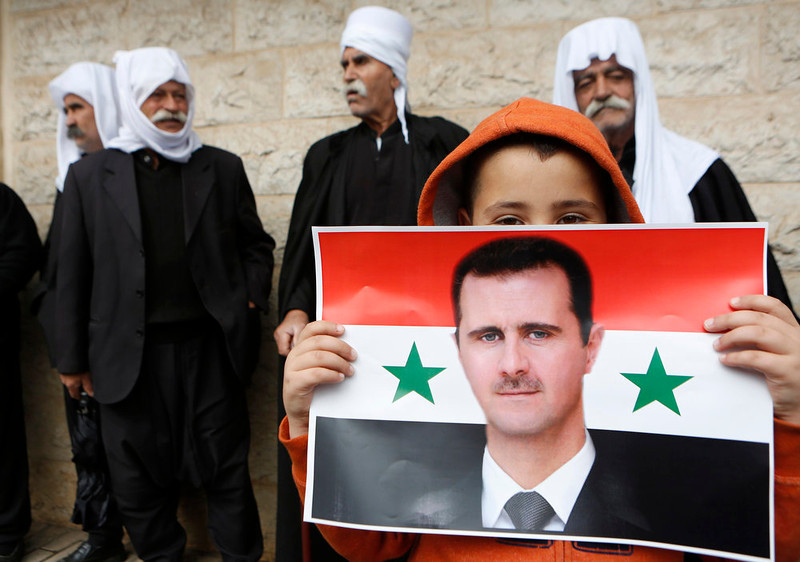 . A boy from the Druze community holds a Syrian flag with the image of Syria\'s President Bashar al-Assad during a rally marking Syria\'s Independence Day in the Druze village of Buqata on the Golan Heights April 17, 2013. Israel captured the Golan Heights from Syria in the 1967 Middle East war and annexed the territory in 1981, a move not recognized internationally. REUTERS/Baz Ratner