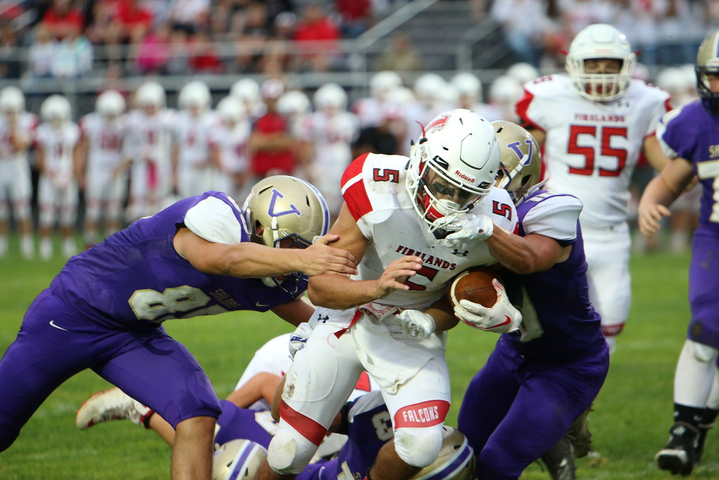. Kyle Sooy - The Morning Journal<br> Firelands\' Blake Ruffner gets wrapped up by the Vermilion defense after a short gain on Sept. 7.