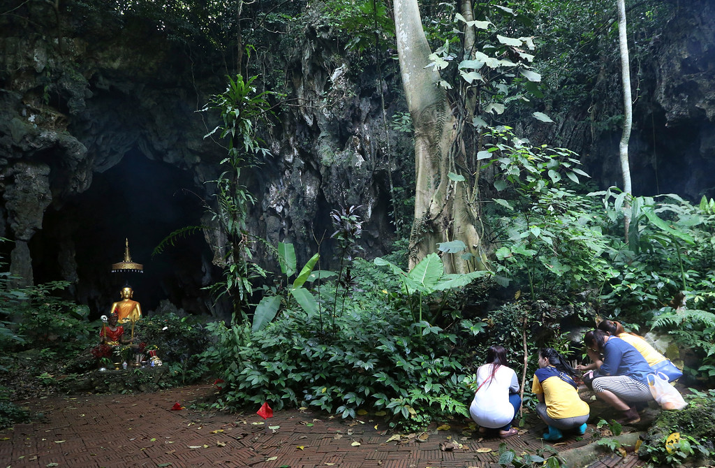 . Family members pray in front of a Buddhist statue near a cave where 12 boys and their soccer coach have been trapped since June 23, in Mae Sai, Chiang Rai province, in northern Thailand Saturday, July 7, 2018. The soccer coach trapped in a cave with 12 Thai boys apologized to their parents in the first letter he and the team have sent out through divers, in which the boys say they\'re doing well and missing their families. (AP Photo/Sakchai Lalit)