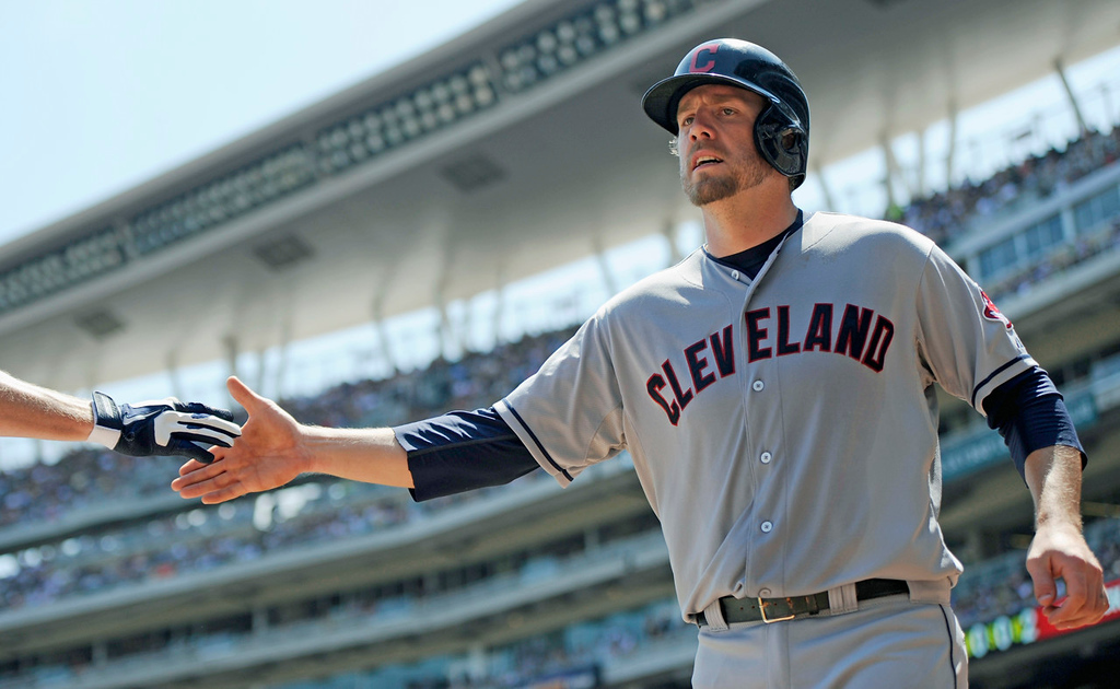 . Cleveland\'s Mark Reynolds gets some skin after scoring the Indians\' first run on a sacrifice fly against the Twins during the second inning. (Photo by Hannah Foslien/Getty Images)