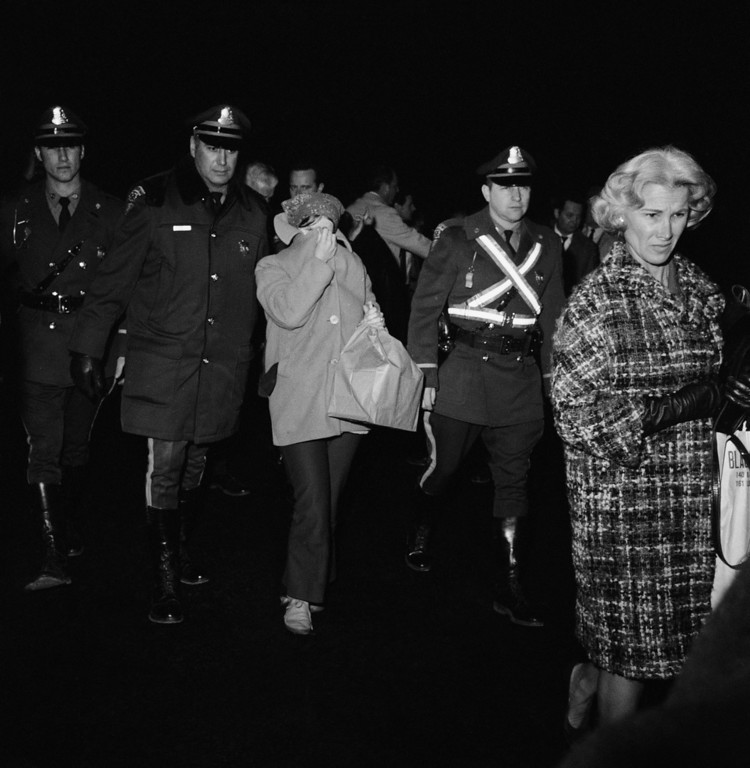 . Linda Kasabian, 20, center, accompanied by Massachusetts State Troopers, looks around her coat collar as she walks to airliner at Logan International Airport, Wednesday, Dec. 3, 1969, Boston, Mass. Miss Kasabian is being returned to California in connection with the slaying of actress Sharon Tate and six others. (AP Photo)