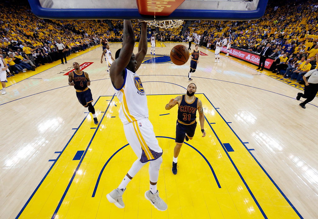 . Golden State Warriors\' Draymond Green, center, dunks against the Cleveland Cavaliers during the second half in Game 1 of basketball\'s NBA Finals Thursday, June 1, 2017, in Oakland, Calif. (AP Photo/Marcio Jose Sanchez)