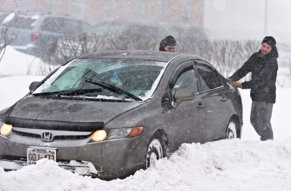 . Two men help out a car that is stuck in the snow on University Street during a snow storm in Moncton, Canada, on Tuesday, Jan. 27, 2015. (AP Photo/The Canadian Press, Marc Grandmaison)