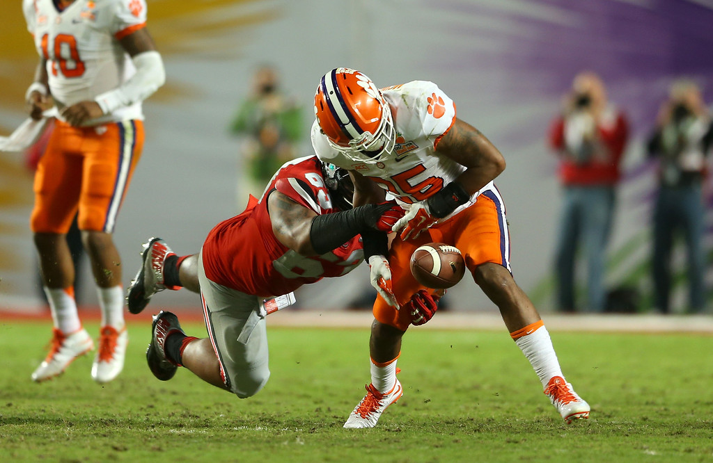 . MIAMI GARDENS, FL - JANUARY 03: Roderick McDowell #25 of the Clemson Tigers fumbles the ball after being hit by Michael Bennett #63 of the Ohio State Buckeyes in the second quarter during the Discover Orange Bowl at Sun Life Stadium on January 3, 2014 in Miami Gardens, Florida.  (Photo by Mike Ehrmann/Getty Images)