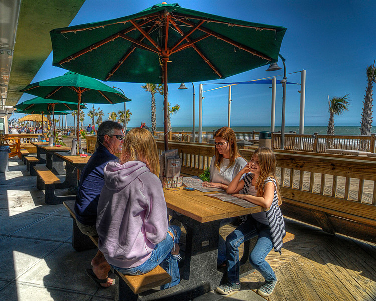 A family orders a meal at the outdoor seating area at Oceanfront Bar & Grill on the Boardwalk in Myrtle Beach, SC on Sunday, March 11, 2012. Copyright 2012 Jason Barnette