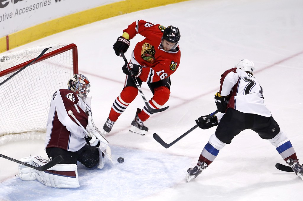 . Colorado Avalanche goalie Semyon Varlamov (1) makes a save on a shot by Chicago Blackhawks center Marcus Kruger (16) as Marc-Andre Cliche (24) also defends during the third period of an NHL hockey game Tuesday, Jan. 6, 2015, in Chicago. The Avalanche won 2-0. (AP Photo/Charles Rex Arbogast)