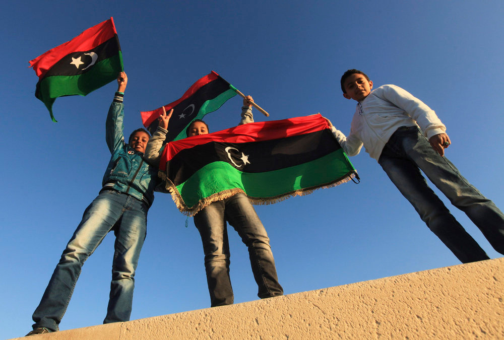 Description of . Boys carry their national flags as they mark the second anniversary of the country's revolution in Benghazi February 16, 2013. The actual second anniversary of the start of the anti-Gaddafi revolt is not until Sunday, but celebrations began on Friday in remembrance of the arrest of a human rights lawyer in Benghazi that kindled the unrest.   REUTERS/Esam Al-Fetori