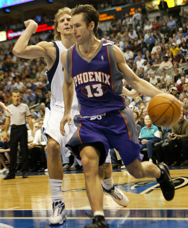 . Phoenix Suns guard Steve Nash (13) from Canada drives past Dallas Mavericks forward Dirk Nowitzki, back, from Germany, in the fourth qyuarter of their game in Dallas, Tuesday, Nov. 16, 2004.  (AP Photo/Donna McWilliam)