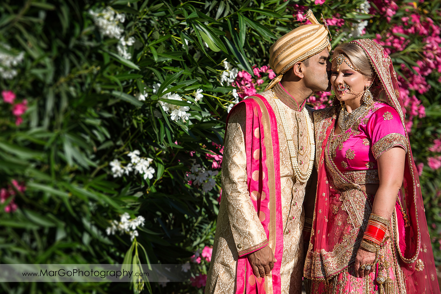 Indian groom kissing bride in pink saree on the wall of white and pink flowers at Elliston Vineyards in Sunol