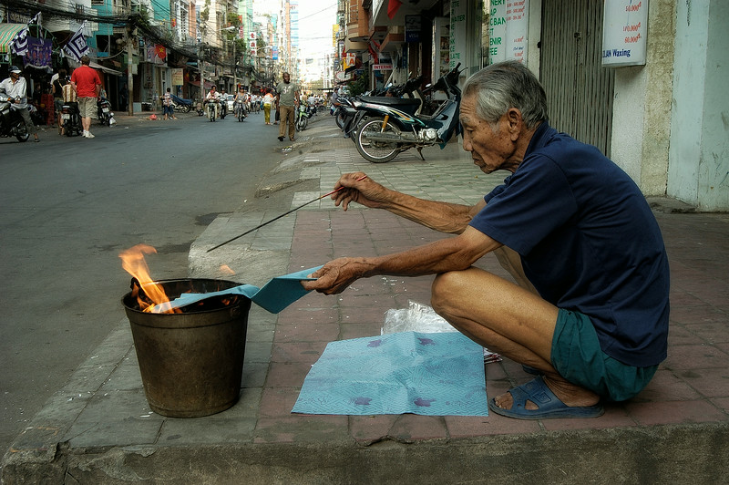 """Tết Trung Nguyên, This festival is viewed as the time for the pardoning of condemned souls who are then released from hell.The """"homeless"""" should be """"fed"""" and appeased with offerings of food. Merits for the living are also earned by the release of birds and fish. This man can be seen burning paper money as an offering to the souls.   Saigon, Vietnam 2008"""