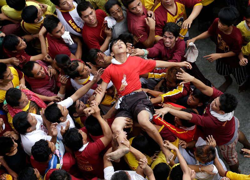 . A Catholic devotee is carried to an ambulance after fainting during the raucous procession of the centuries-old image of the Black Nazarene in celebration of its feast day Wednesday Jan. 9, 2013 in Manila, Philippines. The annual procession is now becoming to be a tourist attraction.  (AP Photo/Bullit Marquez)