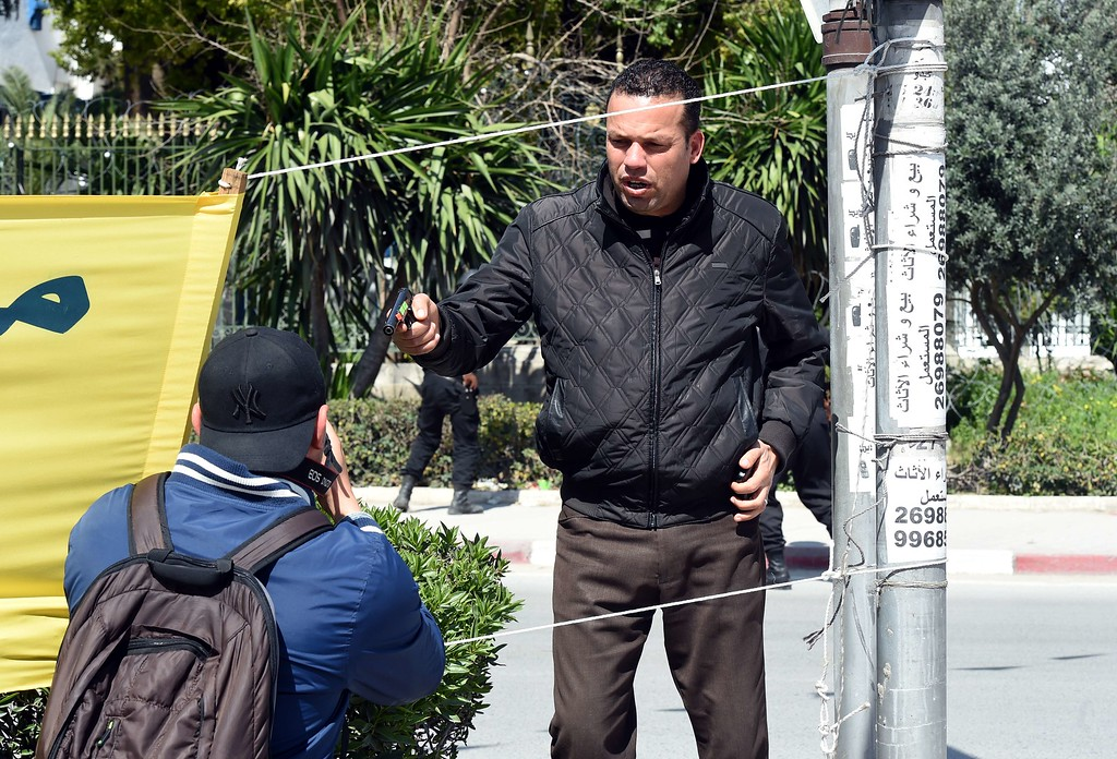 . An armed Tunisian policeman (R) in plainclothes stops a photographer as security forces secure the area after gunmen attacked Tunis\' famed Bardo Museum on March 18, 2015. At least seven foreigners and a Tunisian were killed in an attack by two men armed with assault rifles on the museum, the interior ministry said. AFP PHOTO / FETHI  BELAID/AFP/Getty Images