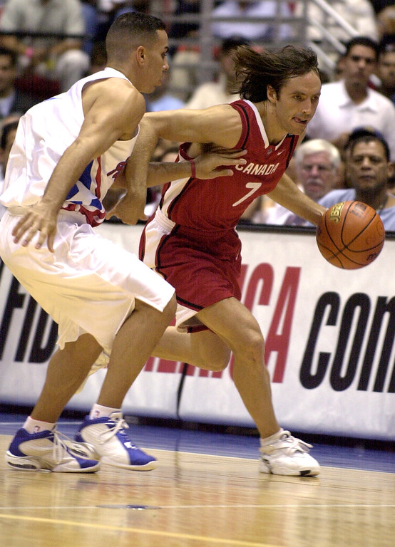 . Steve Nash, right. of Canada, drives the ball past Carlos Arroyo of Puerto Rico during the FIBA Americas Olympic Qualifying Tournament at the Roberto Clemente Coliseum in San Juan, Puerto Rico, Thursday, August 21, 2003.  (AP Photo/Lynne Sladky)