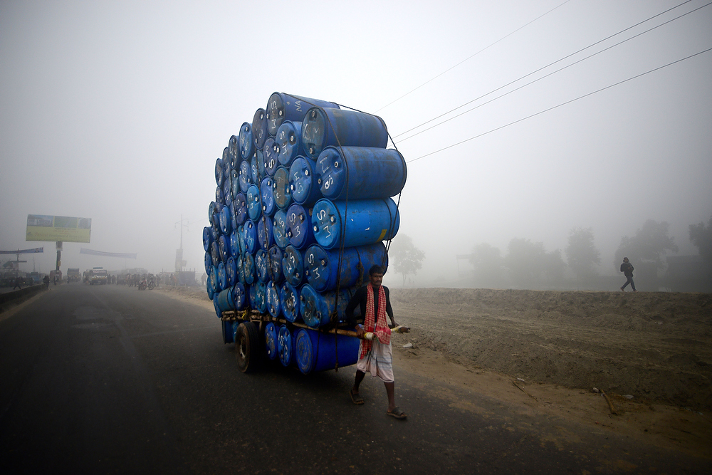 Description of . A Bangladeshi laborer pulls a cart full of empty drums during a nationwide strike in Dhaka on December 20, 2012. Twelve Islamic parties called an eight-hour general strike in the capital Dhaka and a dawn-to-dusk general strike across the country as they seek a ban on left-wing political parties.  MUNIR UZ ZAMAN/AFP/Getty Images