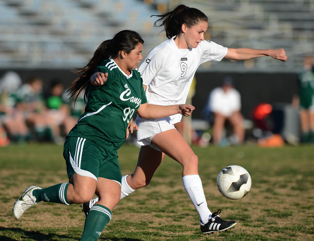 . Peninsula\'s Nicole Phillips (9) tries to center the ball around Canyon\'s Megan Quitevis (99) in a CIF SS Division II first round soccer game Thursday in Rolling Hills Estates. After Peninsula seemingly dominated most of the game, Canyon scored a goal in the final two minutes to win 1-0. 20130214 Photo by Steve McCrank / Staff Photographer