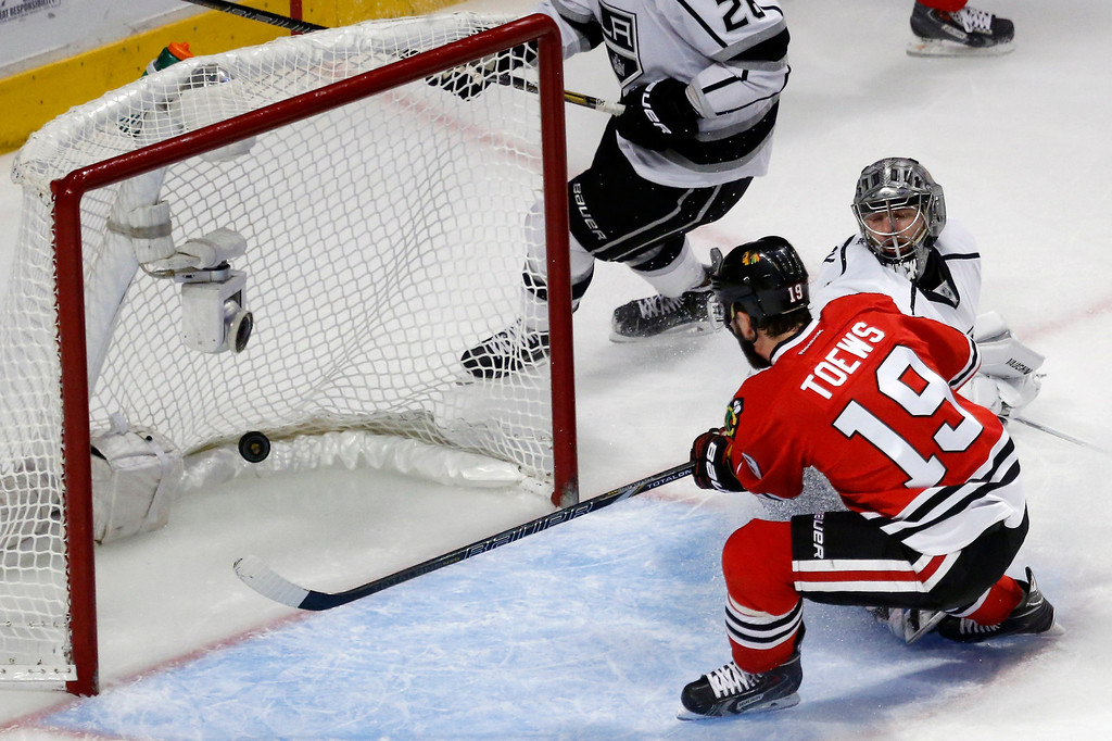 . Chicago Blackhawks center Jonathan Toews (19) scores a goal against Los Angeles Kings goalie Jonathan Quick (32) during the first period in Game 7 of the Western Conference finals in the NHL hockey Stanley Cup playoffs Sunday, June 1, 2014, in Chicago. (AP Photo/Charles Rex Arbogast)