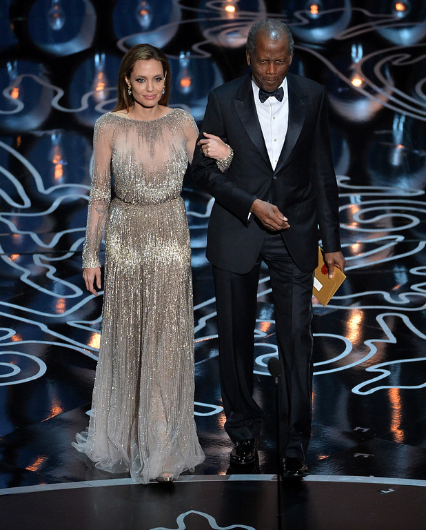 . Actors Angelina Jolie (L) and Sidney Poitier walk onstage during the Oscars at the Dolby Theatre on March 2, 2014 in Hollywood, California.  (Photo by Kevin Winter/Getty Images)