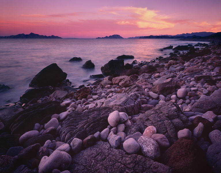 Baja California Sur, Sea, MEX/of Cortez near Loreto. Islands dotting Sea of Cortez with ancient lava and polished stones meeting the sea at sun- set. 290h                      aeb