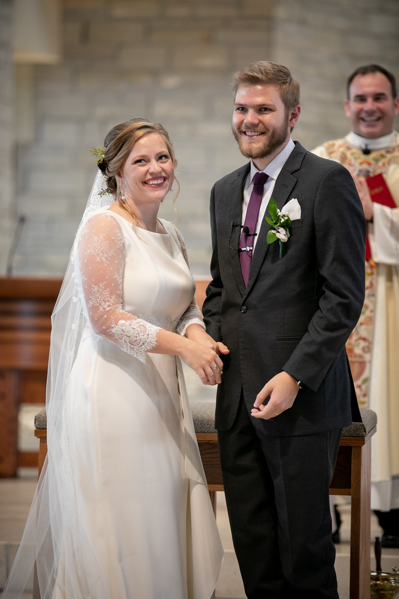 A bride and groom smiling toward the witnesses while standing at the altar