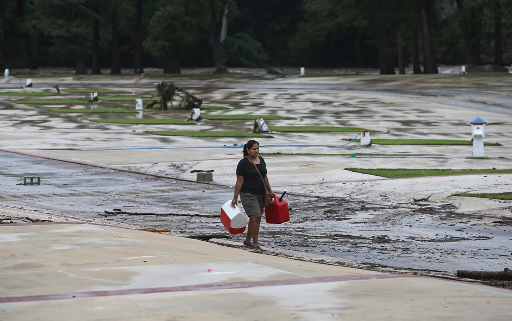 . A woman collects articles strewn over the campground at River Ranch RV Park on the Guadalupe River after the river overflowed its banks in New Braunfels, Texas, on Oct. 31, 2013. The National Weather Service said more than a foot of rain fell in Central Texas, including up to 14 inches in Wimberley, since rainstorms began Wednesday. (AP Photo/San Antonio Express-News, Tom Reel)