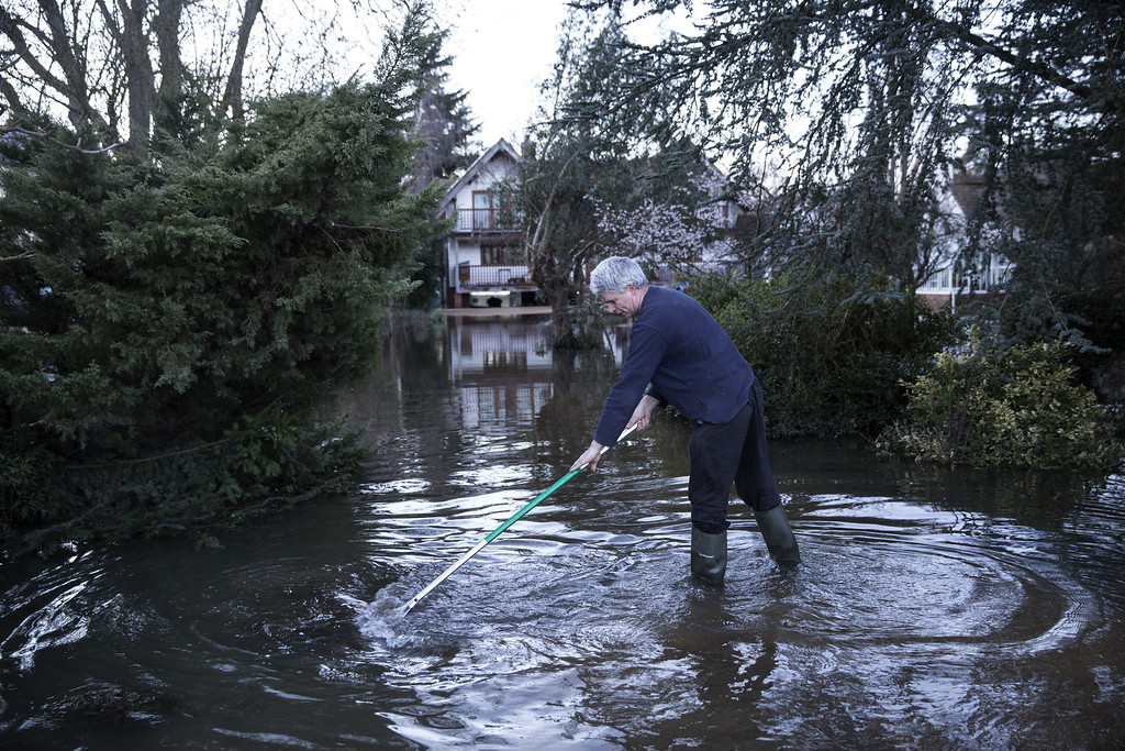 . A man attempts to clear the silt from his property near the river Thames on February 13, 2014 in Wargrave, England. (Photo by Oli Scarff/Getty Images)