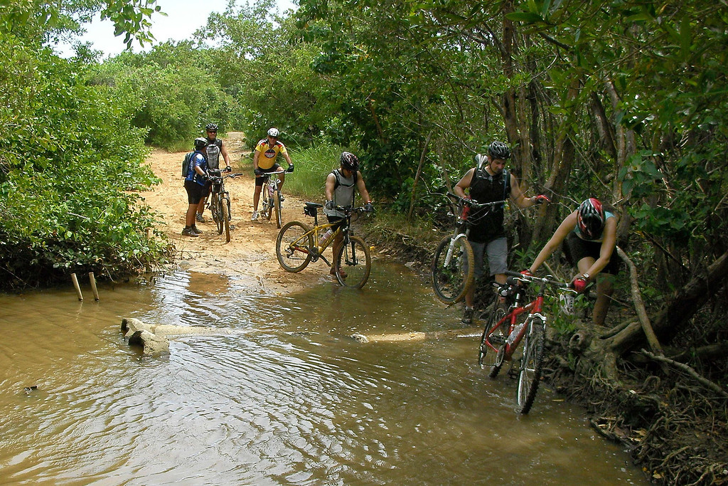 . In this June 28, 2008 photo bikers cross a river in the Northeast Ecological Corridor reserve in the municipality of Luquillo, Puerto Rico.  Puerto Rico\'s Gov. Luis Fortuno revoked on Oct. 30, 2009 this reserve of mountain forests and beaches as part of a drive to bring jobs and investment for the US territory\'s struggling economy, as activists see a broader pattern of looser protection for the island\'s environment. (AP Photo/Ricardo Arduengo)