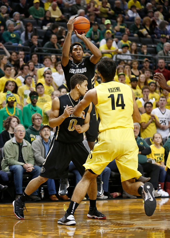 . Colorado\'s Zavier Johnson puts up a three-pointer while teammate Askia Booker defends against Oregon\'s Arsalan Kazemi during the first half of Colorado\'s game against Oregon in an NCAA college basketball game at Matthew Knight Arena in Eugene, Ore. Thursday, Feb. 7, 2013. (AP Photo/Brian Davies)