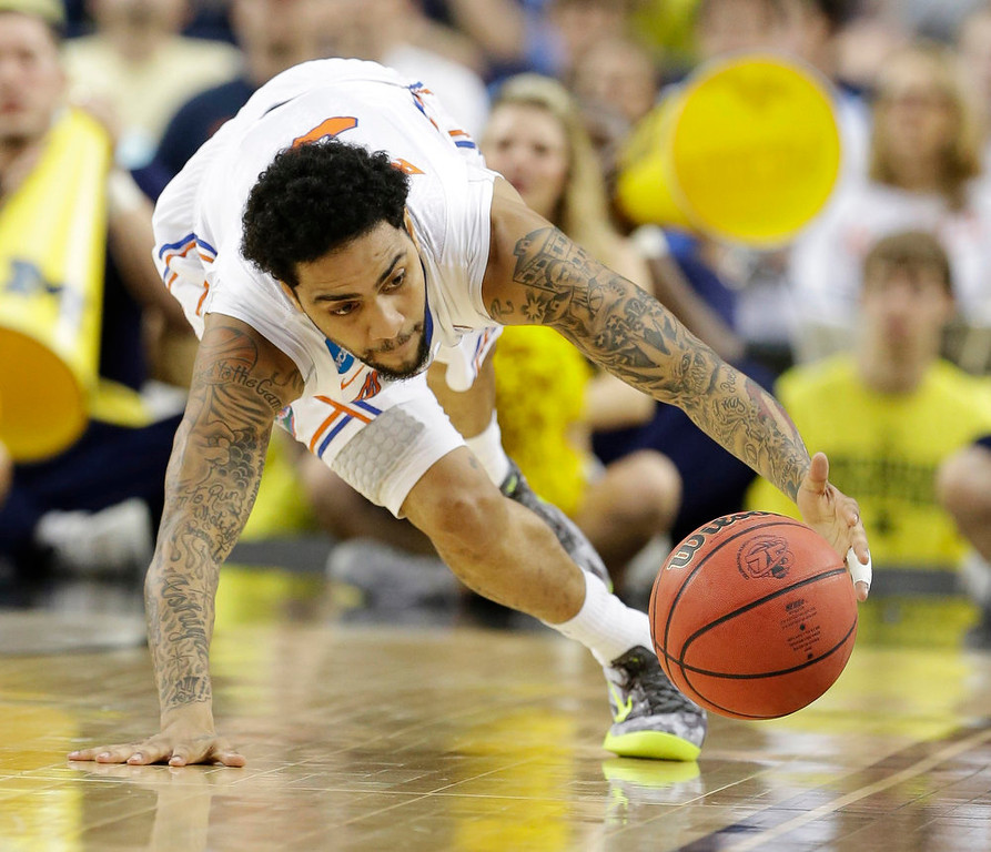 . Florida\'s Mike Rosario (3) grabs a loose ball against Michigan  during the first half of a regional final game in the NCAA college basketball tournament, Sunday, March 31, 2013, in Arlington, Texas. (AP Photo/Tony Gutierrez)