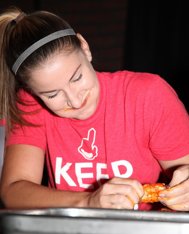 . Carmen Rix of the Hooley House needs to pause and laugh during the wing eating contest on Tuesday.
