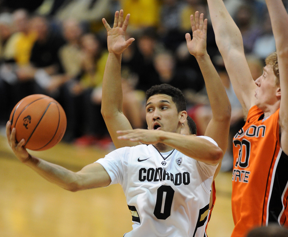 . Askia Booker of CU dishes off as Olaf Schaftnaar of OSU during the second half of the March 9, 2013 game in Boulder.    (Cliff Grassmick/Boulder Daily Camera)