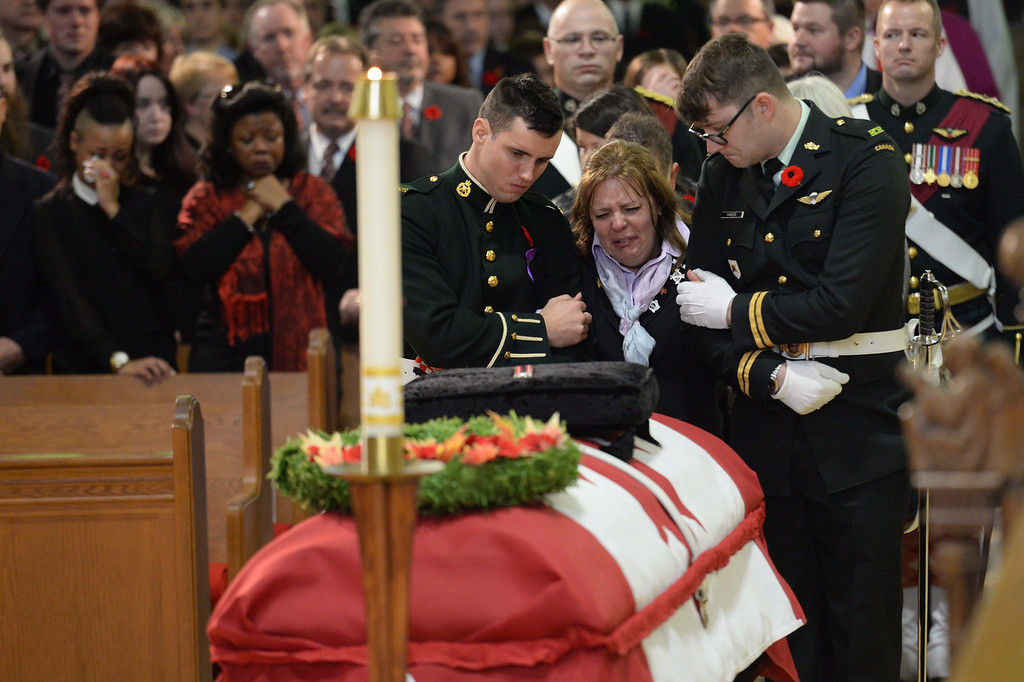 . Kathy Cirillo is comforted in front of the coffin of her son Cpl. Nathan Cirillo at his regimental funeral service in Hamilton, Ontario, on Tuesday, Oct. 28, 2014.   (AP Photo/The Canadian Press, Nathan Denette)