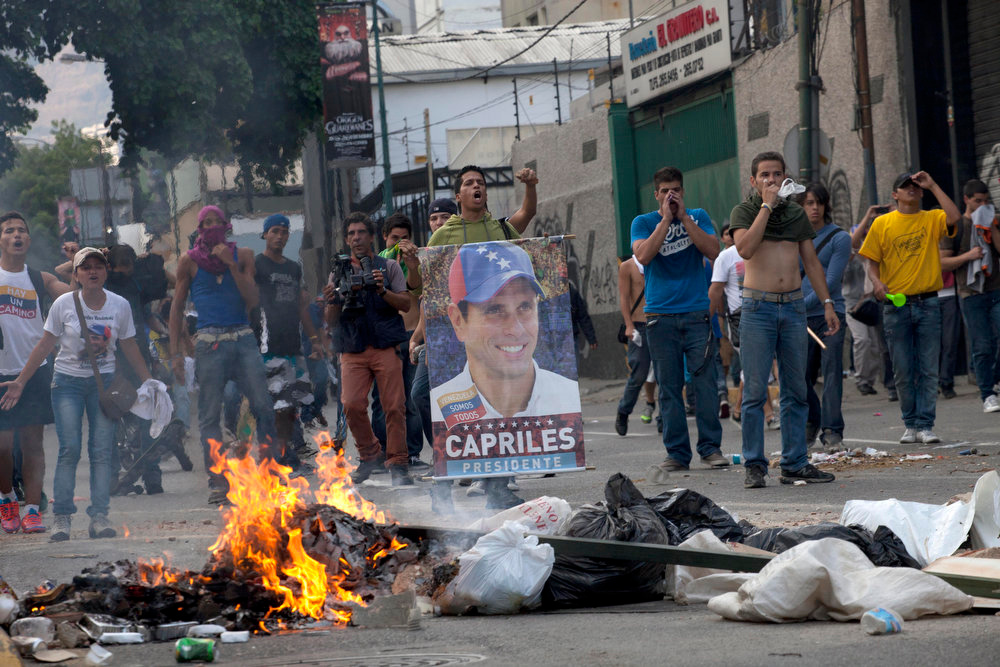 . Demonstrators, one holding a poster of opposition presidential candidate Henrique Capriles, confront riot police from behind a burning barricade in the Altamira neighborhood in Caracas, Venezuela, Monday, April 15, 2013. National Guard troops fired tear gas and plastic bullets to disperse demonstrators protesting the official results in Venezuela\'s disputed presidential election.(AP Photo/Ramon Espinosa)