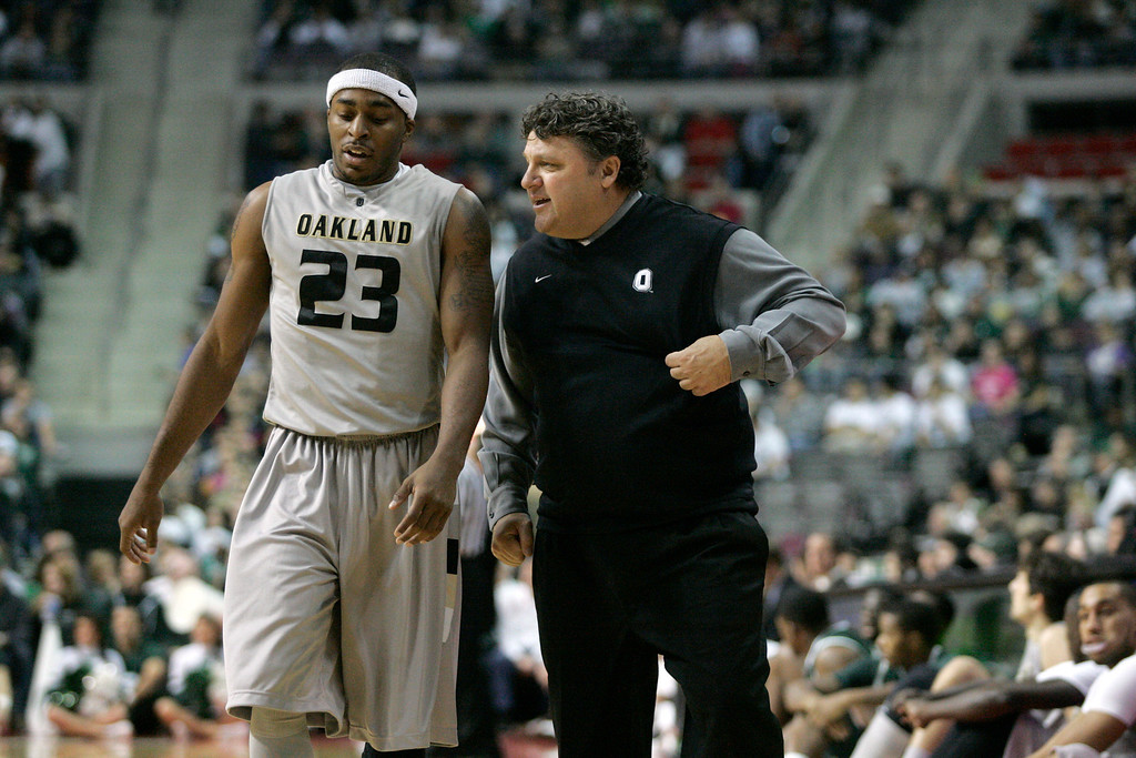 . Oakland coach Greg Kampe, right, talks with guard Reggie Hamilton (23) in the first half of a NCAA college basketball game against Michigan State Saturday, Dec. 11, 2010, in Ann Arbor, Mich. (AP Photo/Duane Burleson)