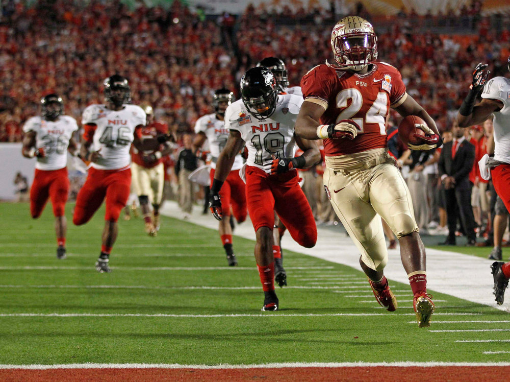 . Florida State Seminoles fullback Lonnie Pryor (R) leads Northern Illinois defenders as he scores a first quarter touchdown in the 2013 Discover Orange Bowl NCAA football game in Miami, Florida January 1, 2013.  REUTERS/Jeff Haynes