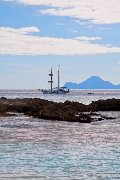 A sailboat enters the harbor near Maho beach.