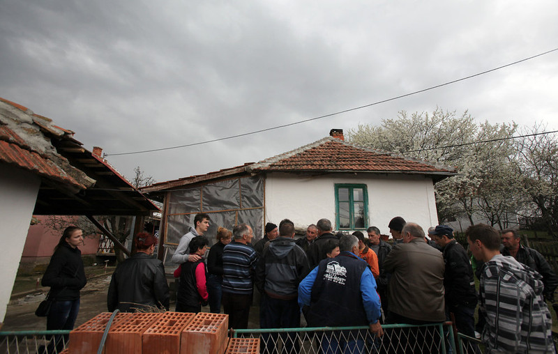 . Locals gathered in front of the house of the Despotovic family whose five members, including a two-year-old, were killed in the shooting spree in the village of Velika Ivanca, Serbia, Tuesday, April 9, 2013. A 60-year-old man gunned down 13 people, including a baby, in a house-to-house rampage in a quiet village on Tuesday before trying to kill himself and his wife, police and hospital officials said. Belgrade emergency hospital spokeswoman Nada Macura said the man, identified as Ljubisa Bogdanovic, used a handgun in the shooting spree at five houses. The dead included six women. (AP Photo/Darko Vojinovic)